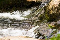 Um córrego tormentoso dos volume de água entre as rochas Imagens de Stock