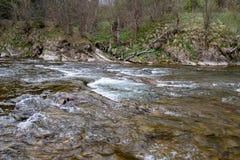 Um c?rrego r?pido no terreno montanhoso ?gua que flui no rio mostrado em uma exposi??o longa fotografia de stock royalty free