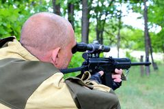 Um caçador do homem está apontando de uma arma na floresta que observa o gu Foto de Stock