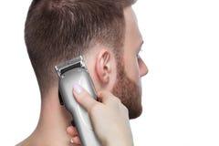 Um cabeleireiro faz um corte de cabelo para um homem novo em um barbeiro fotografia de stock royalty free
