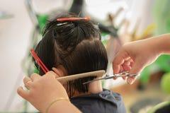 Um cabelo da menina cortado no salão de beleza do barbeiro fotografia de stock royalty free