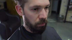 Um cabelo e uma barba do ` s do homem novo cortaram por tesouras na barbearia video estoque