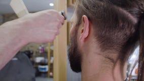 Um cabelo e uma barba do ` s do homem novo cortaram por uma tosquiadeira na barbearia video estoque