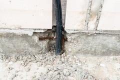 Um cabo de alta tensão elétrico que projeta-se da fundação da casa que está sendo construída imagem de stock