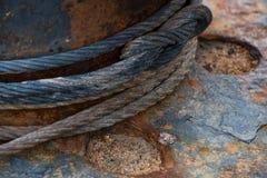 Um cabo do metal amarrado em torno de um bitt oxidado fotografia de stock royalty free