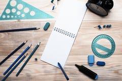 Um caderno branco em um fundo de madeira sobre que uma pena de esferográfica pendurou Há artigos de papelaria na tabela Copyspace Fotografia de Stock