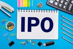 Um caderno com notas IPO, oferta pública inicial com as ferramentas do escritório no fundo azul amarelo Conceito da escolha de IP Fotografia de Stock
