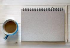 Um caderno com um copo do lápis e de café no fundo de madeira imagem de stock