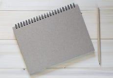 Um caderno com um lápis e esperto no fundo de madeira fotografia de stock