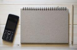 Um caderno com um lápis e um telefone esperto no backgroun de madeira imagens de stock royalty free