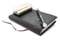 Um caderno e uma pena, grampos de laço Foto de Stock Royalty Free