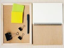 Um caderno espiral vazio com placa do lembrete, nota adesiva, pena, clipes de papel Imagens de Stock