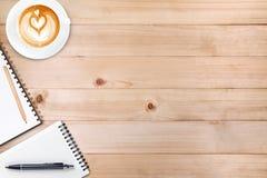 Um caderno vazio aberto com lápis e uma xícara de café em de madeira Fotos de Stock