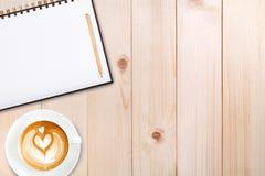 Um caderno vazio aberto com lápis e uma xícara de café em de madeira Imagens de Stock Royalty Free