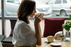 Um café bebendo da mulher bonita nova em um café a jovem mulher no negócio veste-se em uma pausa para o almoço Fotografia de Stock Royalty Free