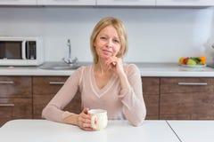 Um café bebendo da mulher superior ativa em casa foto de stock
