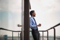 Um café bebendo do trabalhador masculino no balcão do escritório imagem de stock royalty free