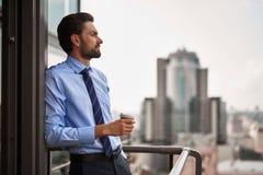 Um café bebendo do trabalhador masculino no balcão do escritório fotos de stock royalty free