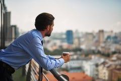 Um café bebendo do trabalhador masculino no balcão do escritório fotografia de stock