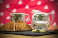 Um café da manhã romântico, leite e uma xícara de café fotos de stock