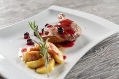 Um café da manhã saudável do confit dos pés do pato com Apple caramelizado serviu em uma placa branca Imagens de Stock Royalty Free