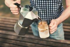 Um café de derramamento do homem em um frasco com leite foto de stock royalty free