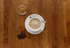 Um café do cappuccino, tiro em um worktop de madeira, com feijões de café Imagem de Stock