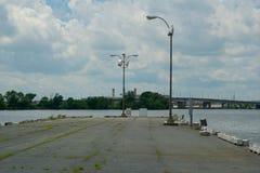Um cais concreto abandonado em um rio com uma ponte atrás dela imagem de stock royalty free