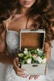 Um caixão, um tronco com as flores nas mãos de uma beleza surpreendente, menina modelo moreno imagem de stock