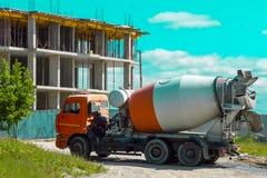 Um caminhão é um caminhão com um táxi da cor alaranjada em um canteiro de obras de uma casa do arranha-céus sob a construção na c imagem de stock