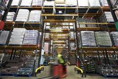 Um caminhão de empilhadeira que passa embora um armazém, borrão de movimento fotos de stock