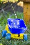 Um caminhão do ` s das crianças na grama O fluxo da água no corpo Foto de Stock Royalty Free