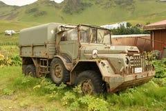 Um caminhão militar abandonado velho no lote de um vizinho de uma cidade pequena em Islândia foto de stock royalty free