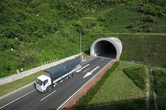 Um caminhão que passa o túnel sob uma montanha fotografia de stock royalty free