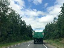 Um caminhão, um trator com um grande reboque verde está conduzindo ao longo de uma estrada asfaltada da floresta com as árvores v fotografia de stock