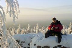 Um caminhante derrama-se chá sobre um penhasco no inverno imagem de stock