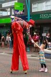 Um caminhante masculino do pernas de pau dobra-se para baixo para agitar as mãos com uma menina fotografia de stock