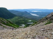 Um caminhante que escala uma inclinação maciça dos seixos na maneira à cimeira de Gros Morne Mountain, em Gros Morne National Par foto de stock