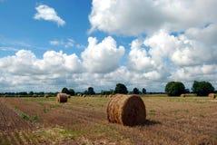 Um campo com monte de feno e as nuvens bonitas Foto de Stock