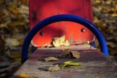 Um campo de jogos com um xaile vermelho para duas crianças Pintura de descascamento velha, outono dourado ensolarado imagens de stock
