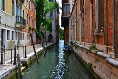 Um canal estreito pequeno em Veneza, gôndola, casas do tijolo fotografia de stock