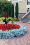 Um canteiro de flores delicioso e bem conservado perto da construção cercada por pedras Imagem de Stock