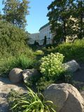 Um canteiro de flores rochoso com flores e arbustos perto de uma grande casa brilhante Imagem de Stock Royalty Free
