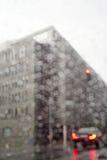 Um canto de um prédio de escritórios no dia chuvoso disparou através de uma janela de carro Fotos de Stock