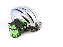 Um capacete biking com luvas em um fundo branco Foto de Stock Royalty Free