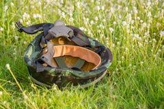 Um capacete militar da camuflagem verde digital no fundo da grama verde Foto de Stock Royalty Free