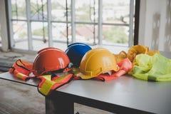 Um capacete que se sente em sua mesa na construção civil Foto de Stock Royalty Free