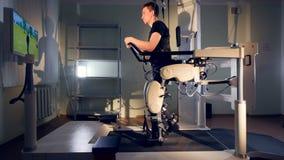 Um caráter da tevê ajuda um usuário do exoskeleton no treinamento vídeos de arquivo