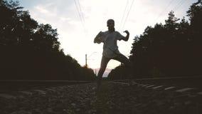 Um cara com jeans rasgados e camiseta dançando hip hop entre a trilha ferroviária contra o sol video estoque