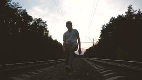 Um cara com jeans rasgados e camiseta dançando krump entre a trilha de trem contra o sol, câmera lenta vídeos de arquivo